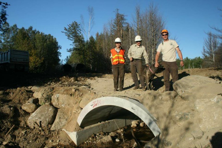 USFWS staff pose in front of a new, fish-friendly culvert in the East Machias.